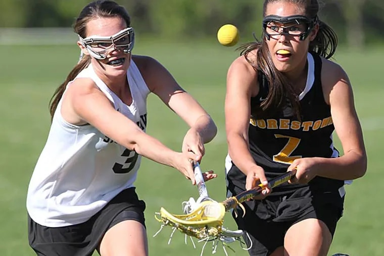 Morgan Glassford, left, of Strath Haven and Anne Keim of Moorestown go after a lacrosse ball in the first half of their game. (Charles Fox/ Staff Photographer)