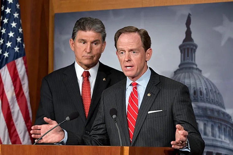 In this April 10, 2013 file photo, Democratic Sen. Joe Manchin of West Virginia, left, and Republican Sen. Patrick Toomey of Pennsylvania, right, announce that they have reached a bipartisan deal on expanding background checks to more gun buyers, at the Capitol in Washington. (AP Photo/J. Scott Applewhite, File)