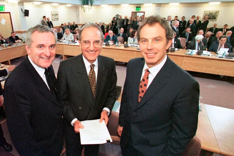 In this April 10, 1998, file photo, from right, British Prime Minister Tony Blair, U.S. Sen. George Mitchell, and Irish Prime Minister Bertie Ahern, pose together after they signed the Good Friday Agreement for peace in Northern Ireland. This set into place a historic power-sharing assembly, devolved from London, and a reduction in the British military's operations in Northern Ireland.