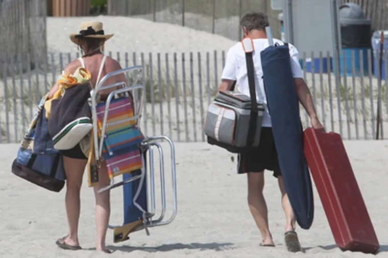 A couple lugs beach chairs and bags from the Cape May Beach near Grant Ave. at the end of the day. (Charles Fox / Staff Photographer)