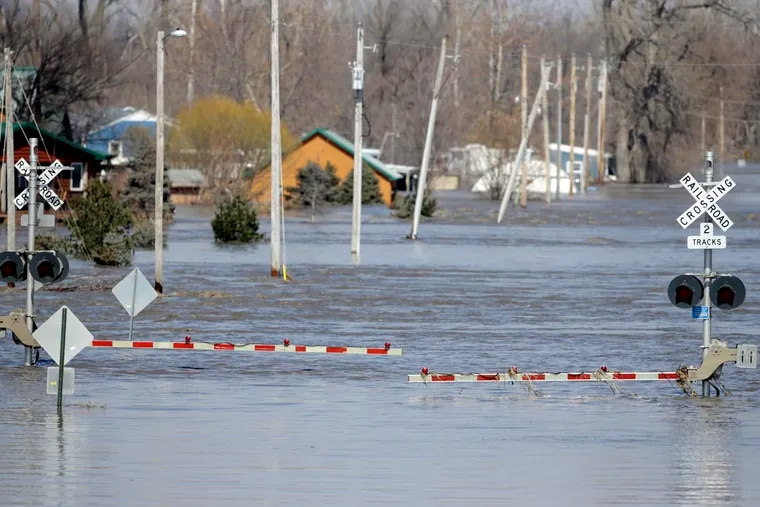 A railroad crossing is flooded with water from the Platte River, in Plattsmouth, Neb., Sunday, March 17, 2019. Hundreds of people remained out of their homes in Nebraska, but rivers there were starting to recede. The National Weather Service said the Elkhorn River remained at major flood stage but was dropping.