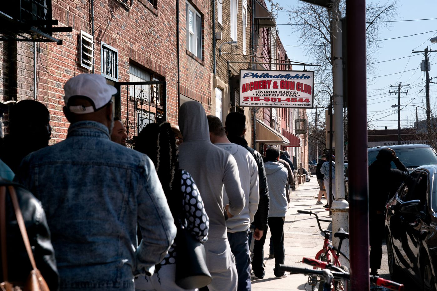 A line of people wait outside of the Philadelphia Gun and Archery Club, in South Philadelphia, March 18, 2020. As of Wednesday morning, nearly 6,500 cases of the coronavirus have been reported in the United States, and 114 people had died. Cities around the United States, including Philadelphia, are increasing social restrictions in an attempt to slow the virus' spread.
