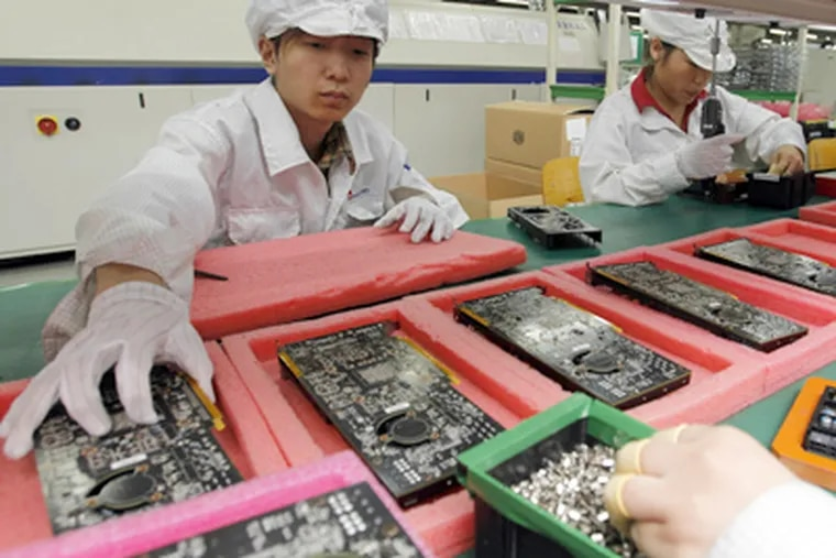 At the Foxxconn complex in Shenzhen, China, workers assemble electronic products. Among the items put together at the numerous factories there are iPods, iPhones, and iPads. (Kin Cheung / Associated Press, File)