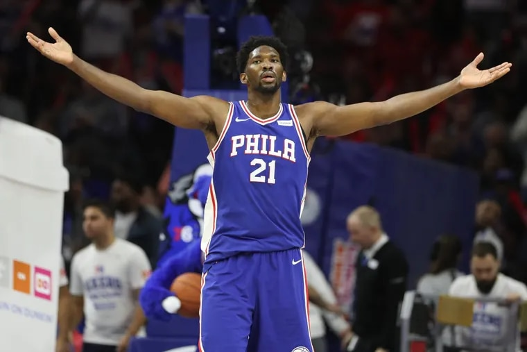 Sixers' center Joel Embiid raises his arms to the crowd at the end of the third quarter against the Trail Blazers on Wednesday.