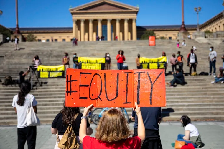 """Debra O'Connor of Philadelphia, holds a sign reading """"#Equity"""" during a rally in honor of Breonna Taylor at the Art Museum steps on Oct. 4."""