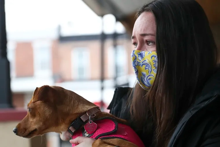 Jelena Loncar, 27, tears up while speaking about her brother, Milan, while holding his dog, Roo, in the Brewerytown section of Philadelphia on Thursday. Milan Loncar, 25, was fatally shot at 31st and Jefferson Streets while walking his dog on Wednesday evening.