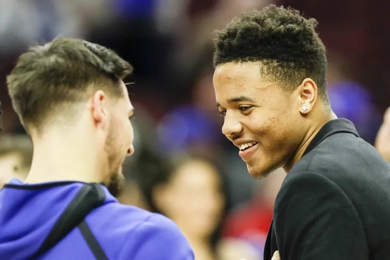 Injured Sixers guard Markelle Fultz with teammate T.J. McConnell (left) before a game last month.