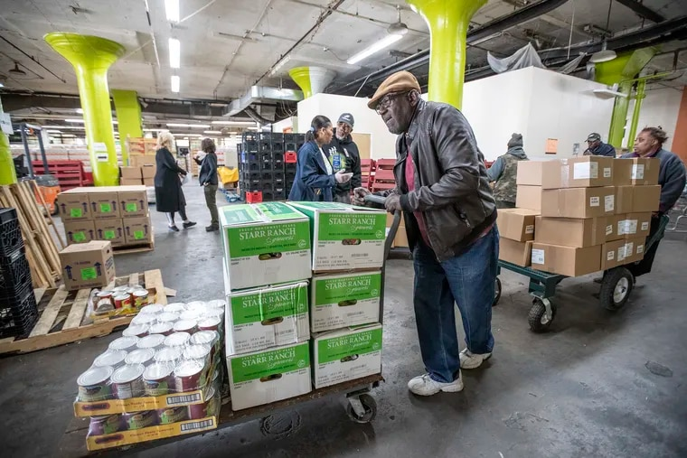 Nate Bonaparte pushes his cart filled with supplies in the warehouse of Share Food Program in Hunting Park. Bonaparte volunteers at the Mount Zion Baptist Church food pantry. The coronavirus may impact the poor hardest, and Share is tripling output to its 500 client pantries to compensate.