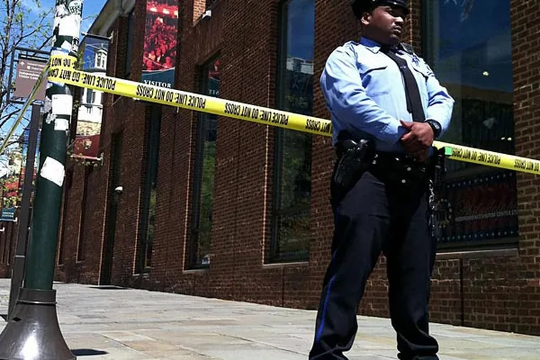 A police officer guards the center at Sixth and Market Streets. The building remained closed for about an hour. (David Maialetti/Staff)
