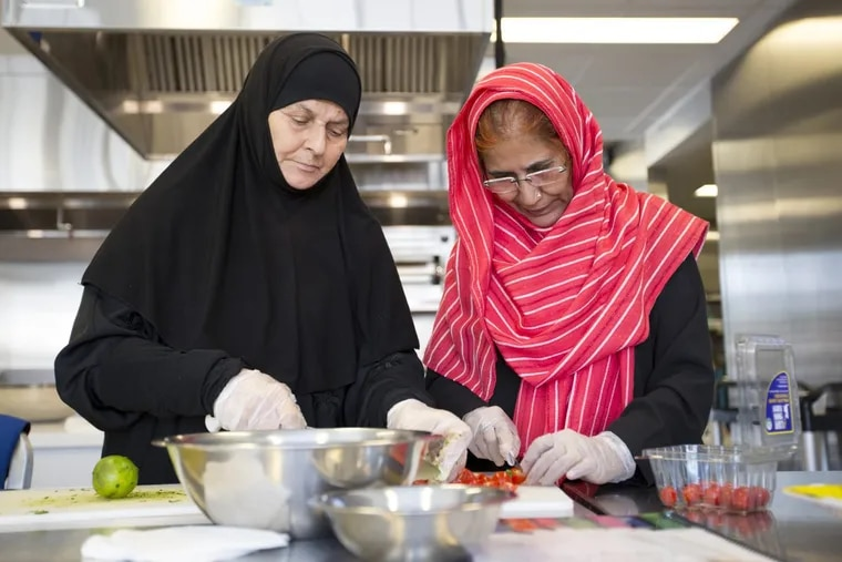 Sameerrah Saved Aldaraji (left), of Iraq, cuts bread with Nilofar Rauf, of Pakistan, at the Culinary Literacy Center at the Free Library of Philadelphia.