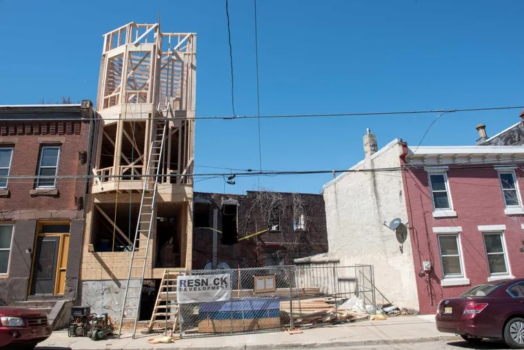 A three-story property is framed on N. 27th Street in Brewerytown in 2017. The neighborhood, once the site of significant disinvestment, has seen plenty of new construction in recent years as developers have purchased and flipped scores of properties and lots.