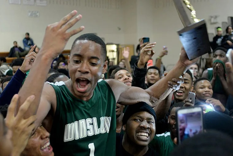 Winslow Township's Michael Cubbage (1) celebrates with the trophy after they defeated Delsea 76-65 in the S.J. Group 3 title game March 10, 2015. (Tom Gralish/Staff Photographer)
