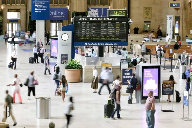 Travelers make their way through 30th Street Station under the long-familiar flip board listing train departures.