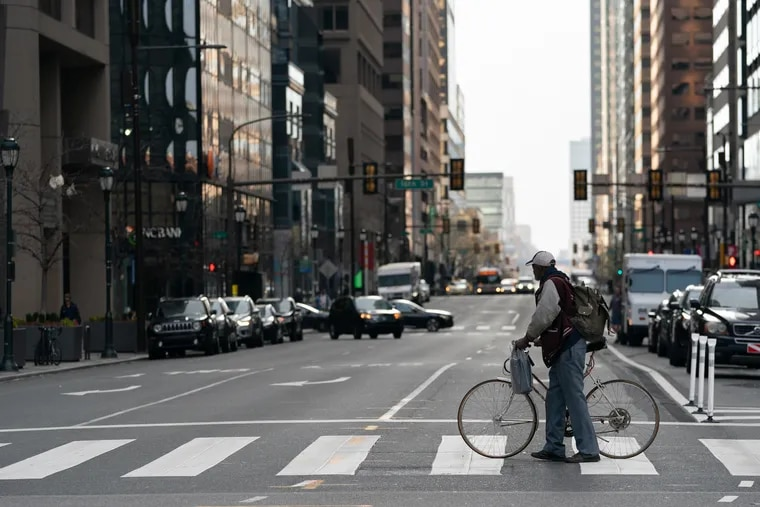 Ervin Johnson walks his bike across Market Street at 15th Street in Philadelphia, on the first day of the shutdown of non-essential businesses.