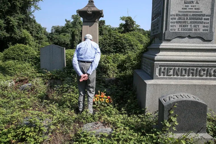 Conrad Schuler, 84, reflects after placing flowers on his brother's grave at Mount Vernon Cemetery. He and family members have had trouble getting into the cemetery over the years because of an absentee landlord. They hope a court-appointed conservator will make it easier.