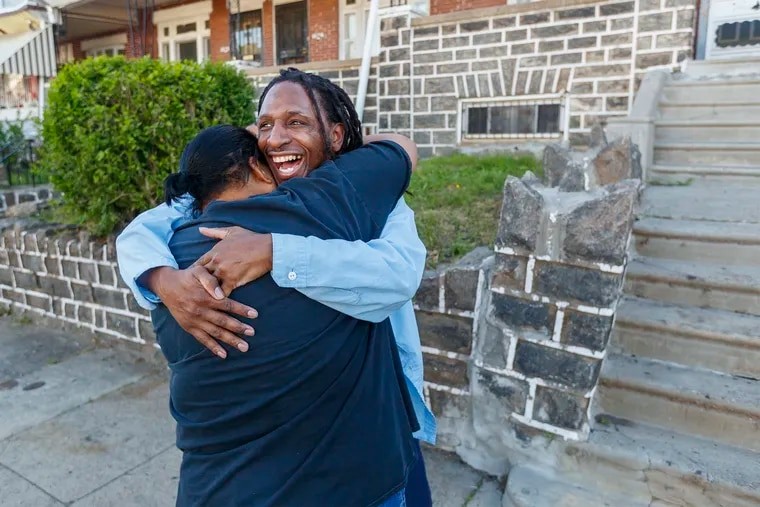 Hassan Bennett, right, is overcome with joy as he hugs his godmother Jacqueline Grasty, left, the moment he arrived back at the home he grew up in on 61st Street.  He has been incarcerated since 2006. On Monday May 6, 2019, Hassan, representing himself, was acquitted in his fourth trial over a 2006 murder.