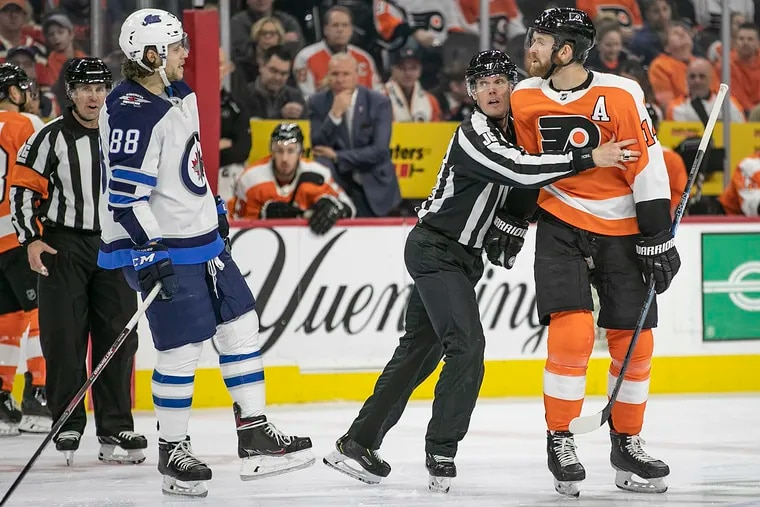 Flyers center Sean Couturier (14) is restrained by the referee while he yells at Jets defenseman Nathan Beaulieu in a Feb. 22 game at the Wells Fargo Center last season. Couturier and the Flyers open the 2021 season Jan. 13 against Pittsburgh.