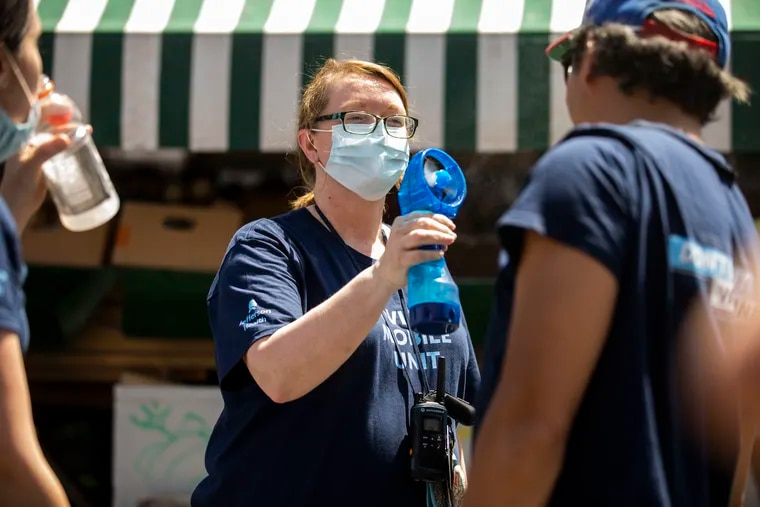 (center) MaryEllen Daley, special projects manager for the health design lab, sprays Dr. Bon Ku with water to cool off during a pop-up COVID-19 vaccination clinic hosted by Jefferson Health outside of South Philly Barbacoa at Ellsworth and South 9th Streets in Philadelphia, Pa. on Sunday, May 23, 2021. Attendees could get a free taco after getting vaccinated.
