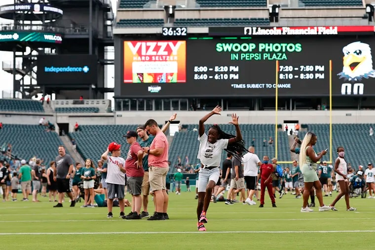 Azziyah Sharpe, 11, of North Philadelphia, runs on the Lincoln Financial Field turf before the Eagles practiced on Sunday.  Fans were allowed on the field before the players practiced.