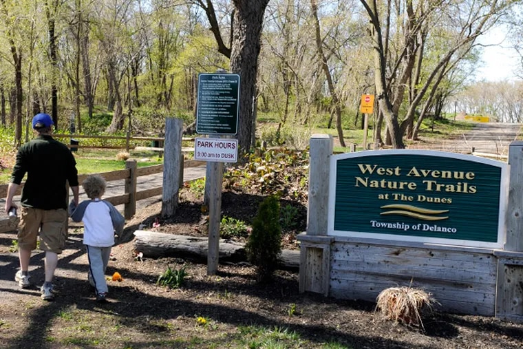 """Joe Kilcoyne, of Middletown, Md., walks with his son Edward, 5, in the Delaware River area of Delanco known as the """"Dunes,"""" April 24, 2014. He grew up in town and was visiting his parents. A judge recently decided the area belongs to NJ, not Delanco, and can be cleared of its woods and hiking trails so that a dumping ground for dredge spoils can be created. (TOM GRALISH/Staff Photographer)"""