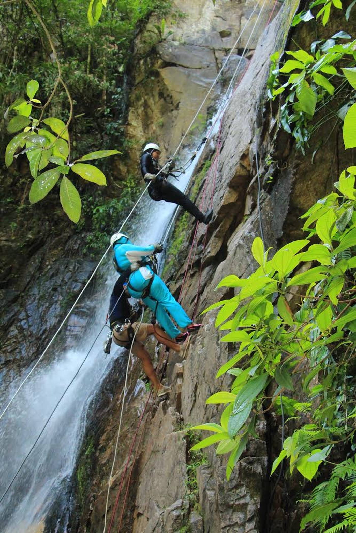 Najlaa Muhammad (in blue) and Ayisha Sims (in black), of the Traveling Muslimahs, rappel down a waterfall with an instructor in Puerto Vallarta, Mexico, June 2018.