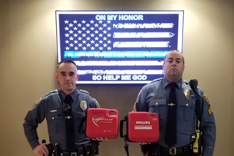 Sgt. Matthew Neely and Ptl. Patrick Morris of the Harrison Township Police Department pose with two of the agency's automated external defibrillators.