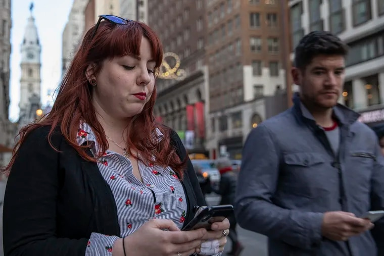 Jess DeStefano, 28, of South Philly, looks at her phone on South Broad Street last week. Fewer people are meeting potential partners in person, using dating apps instead.