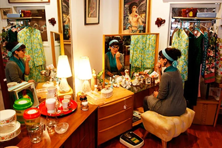 Taryn Zychal, store manager, puts on lip gloss at a Heywood Wakefiled vanity. Era Atomica, 1726 E. Passyunk Avenue, specilizes is mid-century furniture. May 4, 2012. ( MICHAEL S. WIRTZ / Staff Photographer )