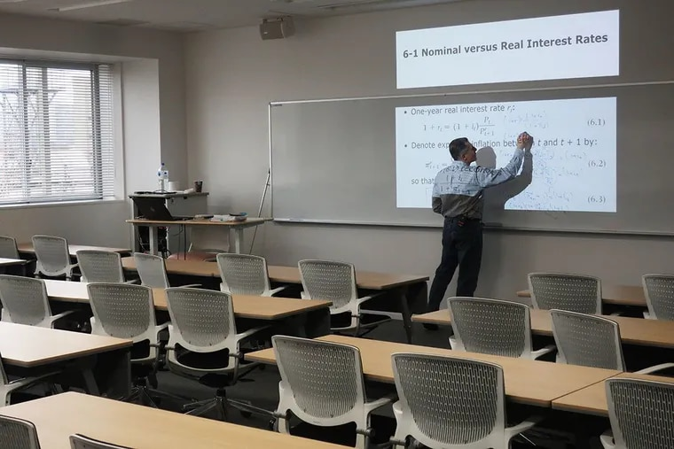 Hady Kahy, a professor at Temple University's Japan campus, teaches Intermediate Microeconomic Analysis in an empty classroom, while his students watch online via a classroom camera.