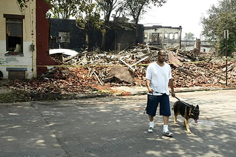 Dennis Missouri and his dog, Cash, walk away Friday from the fire-damaged rubble which was his home 16 years ago along Louis Street in Camden. (Jarid Barringer / Staff Photographer)