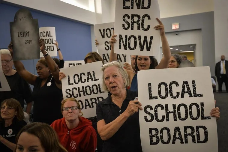 Parents, teachers, and education activists shout and hold signs calling for the end of the SRC during the final School Reform Commission meeting in June.