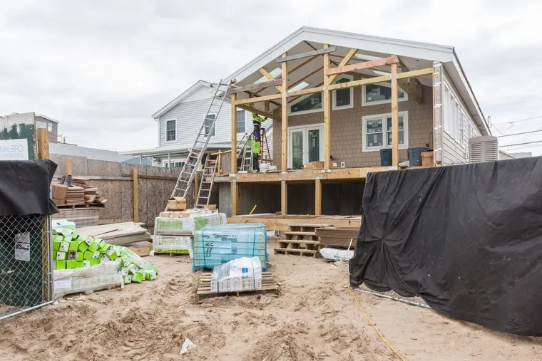 Workers install a gutter during construction of a home designed to withstand extreme weather in the Breezy Point neighborhood of the Queens borough of New York.