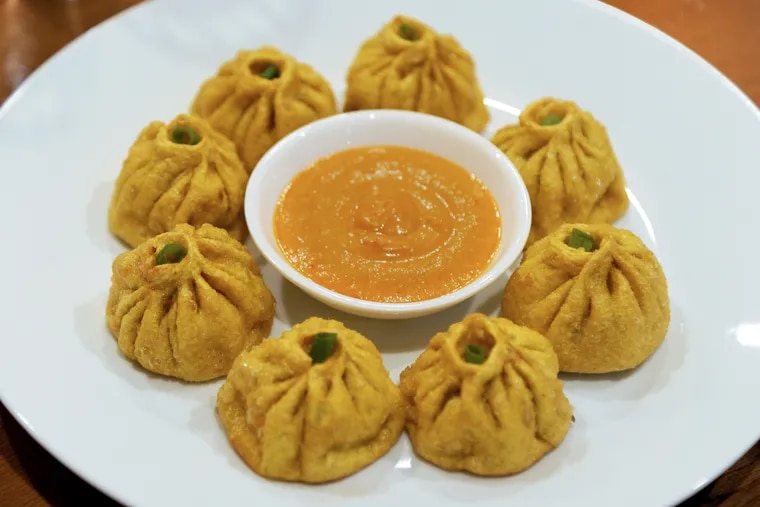 At White Yak, chicken momo dumplings are sparked with celery and scallion and wrapped in top-twisted rounds of dough tinted yellow with carrot juice.