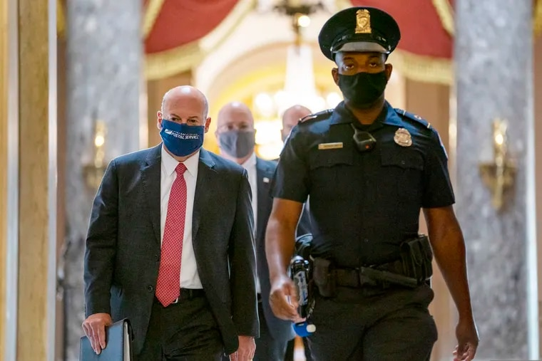 Postmaster General Louis DeJoy, left, shown getting escorted to House Speaker Nancy Pelosi's office on Capitol Hill in Washington on Aug. 5.