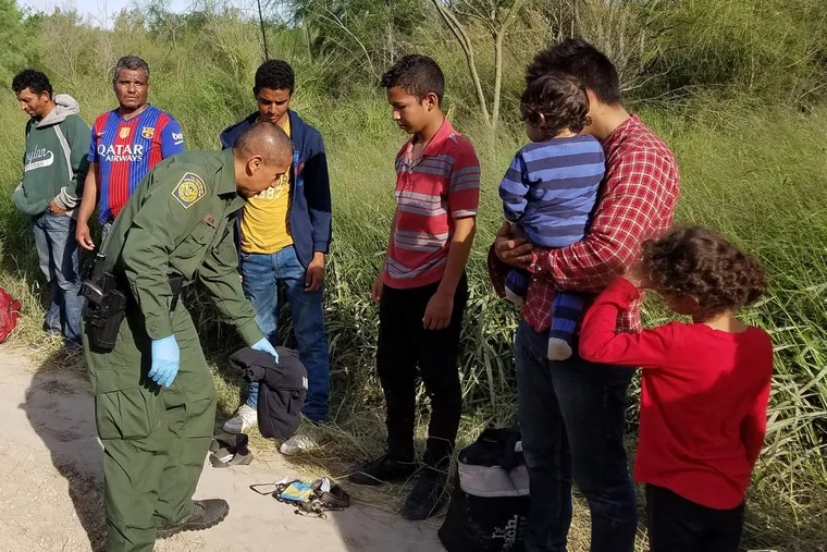 Rio Grande Valley Acting Sector Chief Raul Ortiz, left, observes as agents process a group of 10 Honduran immigrants, including two children and a baby in a blue striped onesie trying to cross the border near Anzalduas Park in Mission, Texas. (Molly Hennessy-Fiske/Los Angeles Times/TNS)