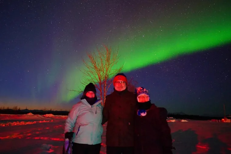 Left to right, Celia, Paul, and author, Monica Gondek standing in Bettles, Alaska, 35 miles above the Arctic Circle at 11 p.m. in March ,2017, looking at the Northern Lights.