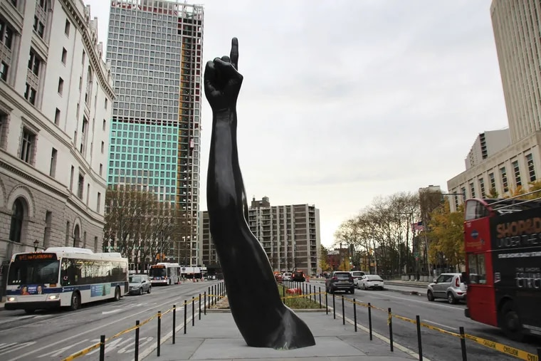 """The work """"Unity"""" by the US artist Hank Willis Thomas. The sculpture consists of an almost seven-meter-high arm with a hand and an outstretched index finger, modeled after Joel Embiid.  It has recently been placed on the central strip of a street in the Brooklyn district, very close to the Brooklyn Bridge."""