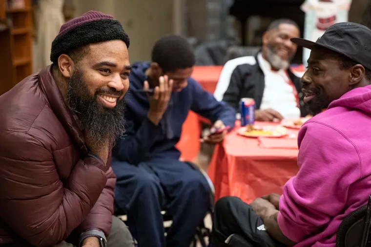 Jalil Frazier, left, laughs with John Muldrow, right, during the gunshot survivors group at the Carousel House in West Philadelphia on Monday, Dec. 16, 2019. The group was having a holiday party for its final meeting of the year.
