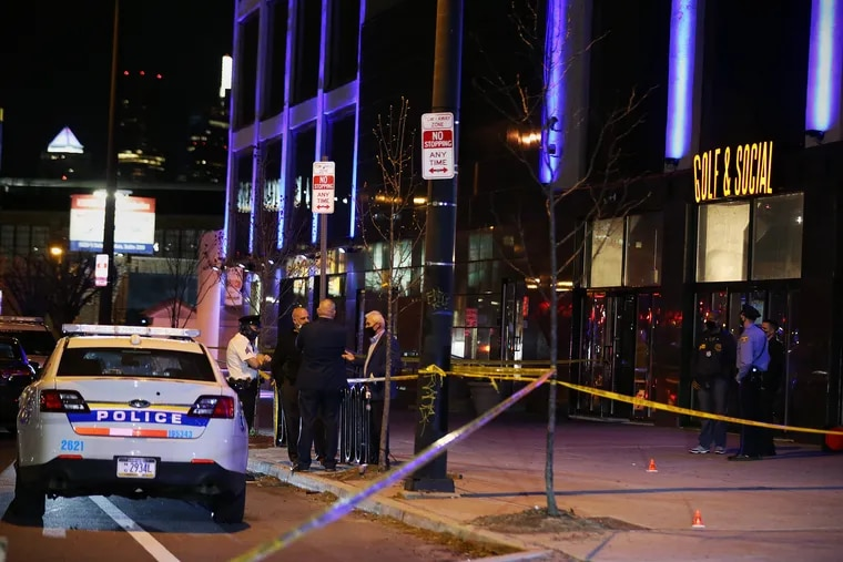 Police investigate the scene where multiple people were shot outside the Golf & Social bar on the 1000 block of North Delaware Avenue in Philadelphia's Fishtown section on March 26. Police have arrested a 16-year-old in connection with the incident.