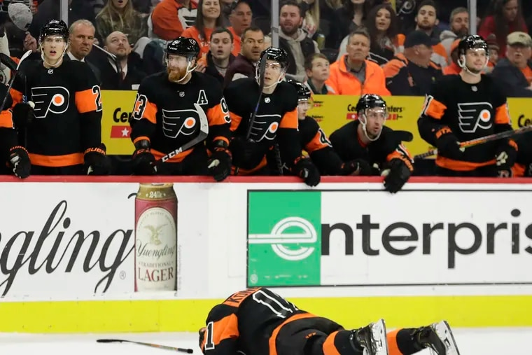 Flyers right wing Travis Konecny lays on the ice after getting hit by Ottawa defenseman Mark Borowiecki on Saturday.