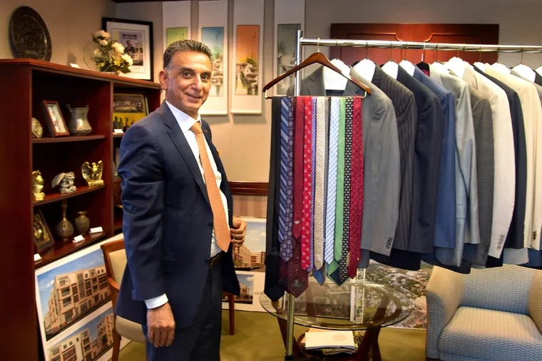 """Rowan University president Ali Houshmand in his Glassboro campus office with some of the suits and ties he is donating for students in need of proper attire for a job interview. He has issued a 100-day challenge to Rowan students to fill the university's """"Suit Our Students Career Closet"""" for students who may not be able to afford proper attire for job interviews. TOM GRALISH / Staff Photographer"""