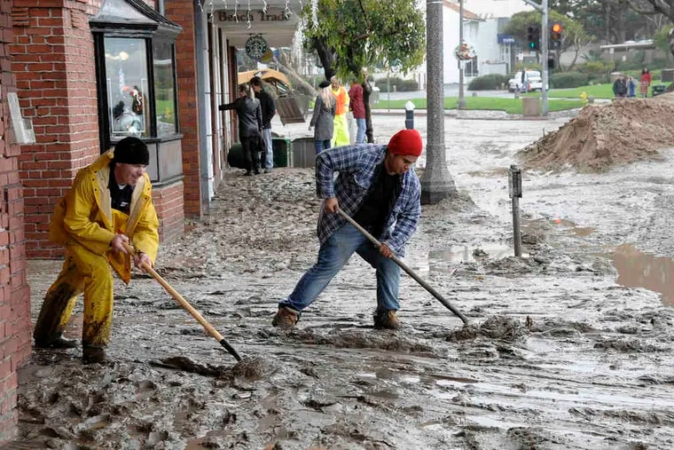 Workers shovel mud out onto the Pacific Coast Highway from the entrance to a movie theater in Laguna Beach, Calif. Los Angeles County residents were warned through Thursday to steer clear of contaminated water around storm drains, creeks, and rivers.