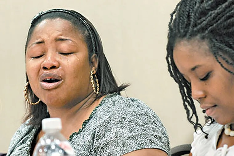 At Rutgers Camden, Tisha Oliver cries as she talks about her experience as the child of an incarcerated parent. At right is her sister, Pennie Oliver. (April Saul / Staff Photographer)