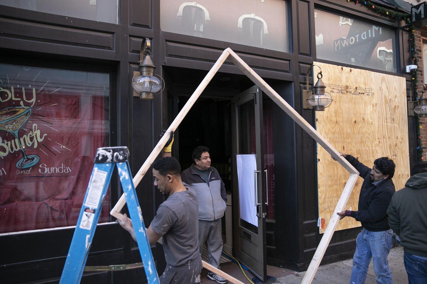 Fearing 'desperate people' during coronavirus shutdown, bar owner boards up windows in Center City