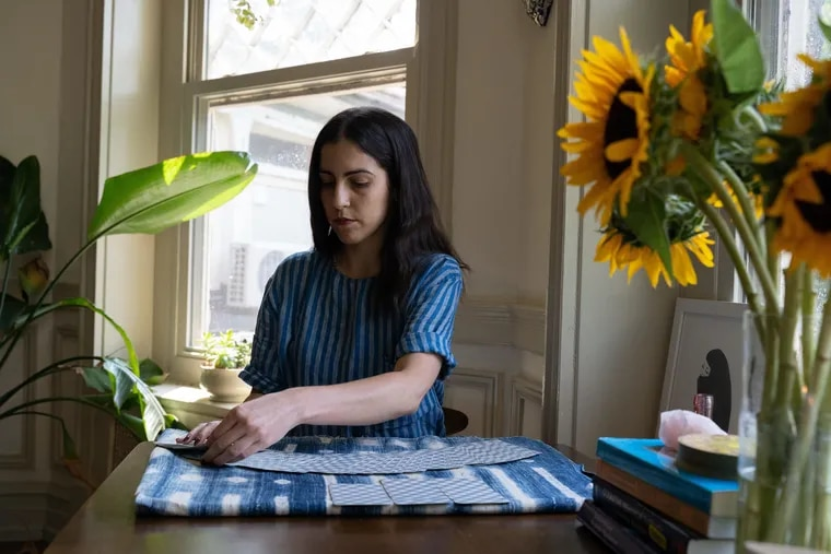 Jessica Dore, a graduate student of clinical social work, shuffles her tarot cards, which she uses to discuss concepts surrounding mental health.