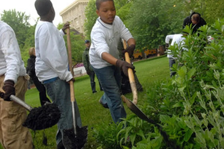 Jordan Ross (facing camera), 10, of Germantown, helps his fellow participants in the First Bloom program tidy up a planting bed on the grounds behind Carpenters Hall.