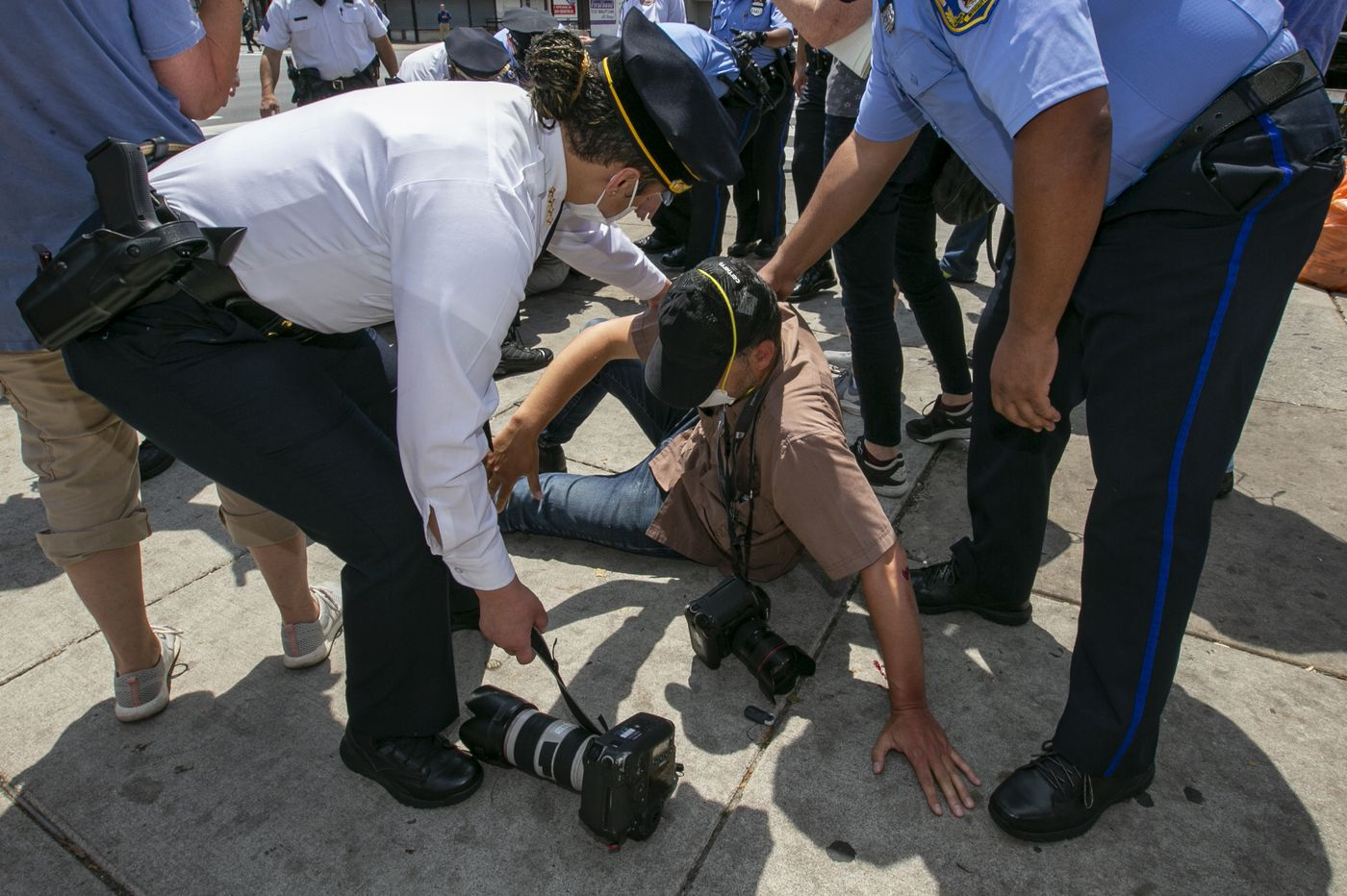 A news photographer was punched and knocked to the ground. Commissioner Outlaw was one of the officers who responded.