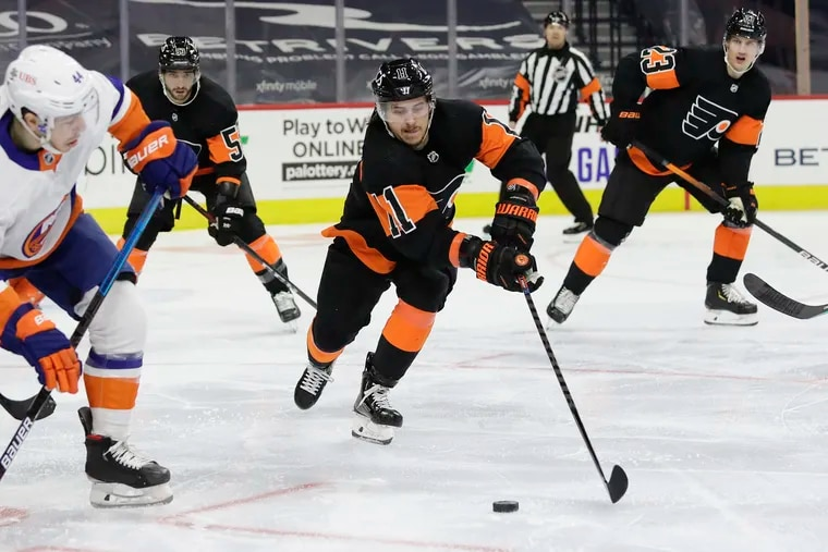 Flyers right winger Travis Konecny reaches for the puck against New York Islanders center Jean-Gabriel Pageau during a game last month. Konecny was placed on the COVID-19 protocol list Sunday.