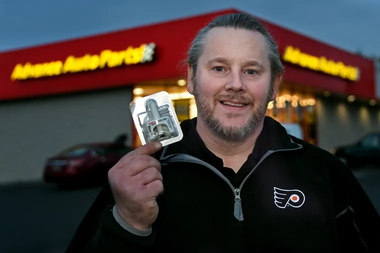 Bill Kinkle poses with naloxone outside the auto parts store where he works in Glenside