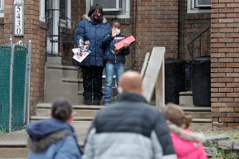 Latyia Johnson looks on as her 7 year old son Rasul Bey waves to the Lerman family (in foreground) after they left  a Nintendo Switch at the front door of Rasul's home.